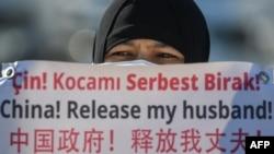 一名维吾尔妇女在中国驻伊斯坦布尔领事馆附近举牌抗议,要求中国政府释放其丈夫。(2021年2月22日)