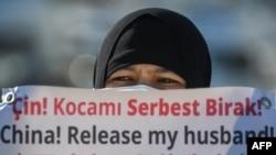 一名維吾爾婦女在中國駐伊斯坦布爾領事館附近舉牌抗議,要求中國政府釋放其丈夫。(2021年2月22日)