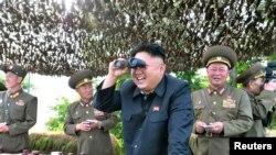 Lãnh tụ Bắc Triều Tiên Kim Jong Un dùng ống nhòm quan sát trận địa với các tướng lãnh.