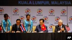 Thai Prime Minister Prayuth Chan-ocha, left, and Vietnam's Prime Minister Nguyen Tan Dung, center, sign documents as Malaysia's Prime Minister Najib Razak looks on during the signing ceremony of the 2015 Kuala Lumpur Declaration on the Establishment of th