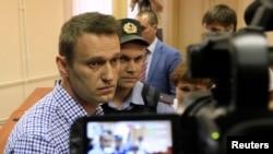2013年7月18日,俄罗斯反对派领袖阿利克塞•纳瓦尔尼在内政部警卫看守下进入法庭。