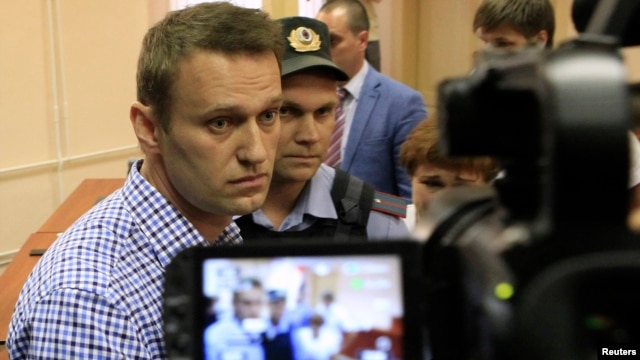 Russian opposition leader Alexei Navalny (L, front) is escorted by an Interior Ministry officer inside a courtroom in Kirov, July 18, 2013.