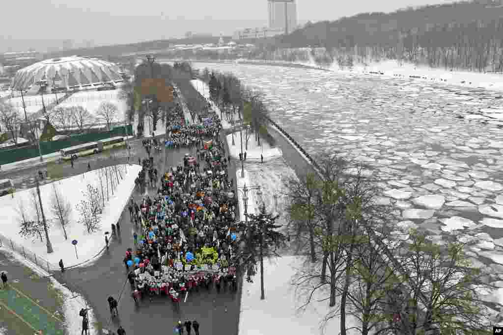 People take part in a procession along Frunzenskaya quay to support presidential candidate and Russia's current Prime Minister Vladimir Putin on the Defender of the Fatherland Day near the Moskva River in Moscow, February 23, 2012. (Reuters)