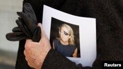 Một người đàn ông cầm bức ảnh phóng viên Marie Colvin của báo Sunday Times sau buổi lễ tưởng niệm ở London, ngày 16 tháng 5 năm 2012.