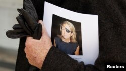 FILE - A man holds a sign honoring Sunday Times journalist Marie Colvin after a memorial service, outside St. Martin in the Field in London, May 16, 2012.