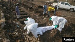 Health workers bury the body of a suspected Ebola victim at a cemetery in Freetown, Sierra Leone, Dec. 21, 2014.