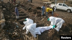 Health workers bury the body of a suspected Ebola victim at a cemetery in Freetown, Dec. 21, 2014.