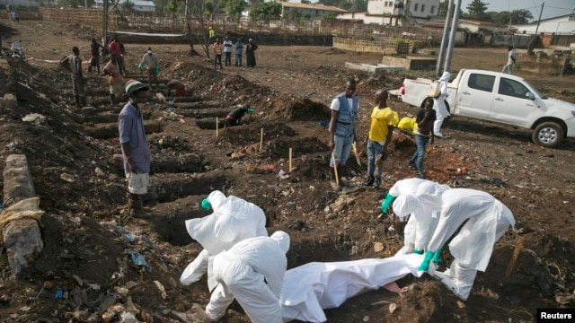 FILE - Health workers bury the body of a suspected Ebola victim at a cemetery in Sierra Leone, Dec. 21, 2014.