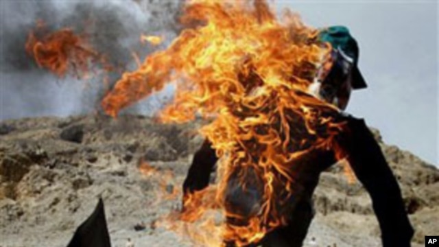 An Afghan protester holds a burning effigy of American pastor Terry Jones during a demonstration in  Nangarhar province, Afghanistan, April 4, 2011.