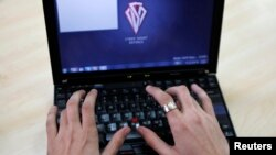 FILE - Romanian Razvan Cernaianu, formerly known as a hacker by the name of TinKode, works at his laptop in his office in Bucharest in this March 15, 2013 picture.