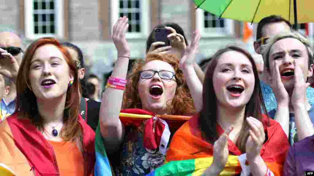Para pendukung pernikahan sesama jenis bersorak di Kastil Dublin saat menunggu hasil referendum (23/5). (AFP/Paul Faith)