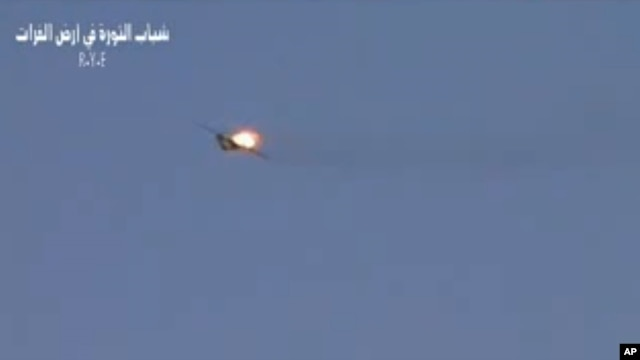 This image made from amateur video released by R.Y.E. Syria purports to show a Syrian plane downed over the eastern province of Deir el-Zour, Syria, August 13, 2012.