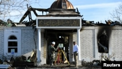 Security officials investigate the aftermath of a fire at the Victoria Islamic Center mosque in Victoria, Texas, Jan. 29, 2017.
