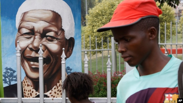 A child looks through a fence at a portrait of former president Nelson Mandela in a Park in Soweto, South Africa, Mar. 28, 2013.
