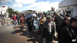People carry their belongings after they fled Libya at the Tunisia-Libya border, near the village of Ras El Jedir, Tunisia, Feb. 24, 2011