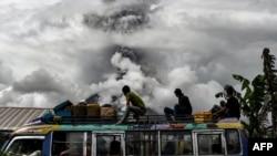 FILE - Indonesian bus passengers watch as Mount Sinabung spews thick smoke in Karo, North Sumatra, Jan. 2, 2018.