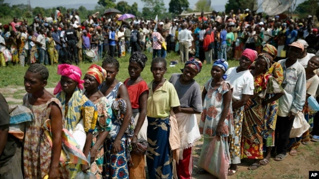 Internally displaced people wait for rations at a World Food Program distribution point near a makeshift camp  set up in Bangui, Central African Republic, Dec. 13, 2013.