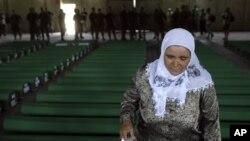 Seorang wanita mencari peti jenasah angoota keluarganya di antara 520 peti jenasah yang berhasil diidentifikasi sebagai korban Srebrenica di kompleks peringatan Potocari dekat Srebrenica, 160 kilometer sebelah timur Sarajevo, Bosnia dan Herzegovina (10/7