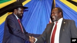 FILE - South Sudan's President Salva Kiir, left, shakes hands with rebel leader and former vice president Riek Machar after signing an agreement to reunify their political party in Arusha, Tanzania, Jan. 21, 2015.