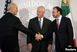 U.S. Secretary of State Rex Tillerson (center) looks at Secretary of Homeland Security John Kelly as he shakes hands with Mexico's Foreign Secretary Luis Videgaray (right) after delivering statements at the Ministry of Foreign Affairs in Mexico City, Feb. 23, 2017.