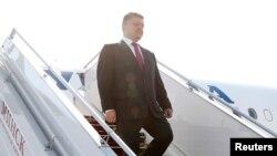 Presiden Ukraina Petro Poroshenko menuruni tangga pesawat saat tiba di Minsk (26/8).