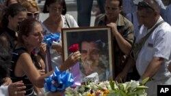 Bà Ofelia Acevedo, vợ nhà hoạt động Oswaldo Paya, đặt 1 bông hoa lên quan tài của chồng mình tại 1 nghĩa trang ở Havana, Cuba, 24/7/2012