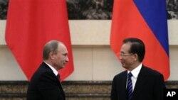 俄罗斯总理普京(左)10月11日在北京人民大会堂与中国总理温家宝握手