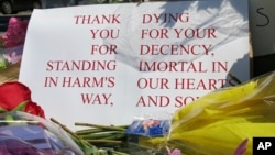 A sign of thanks rests against a traffic light pole at a memorial outside the transit center in Portland, Ore., May 27, 2017. People stopped with flowers, candles, signs and painted rocks for two bystanders who were stabbed to death Friday while trying to stop a man who was yelling anti-Muslim slurs and acting aggressively toward two young women on a light-rail train in Portland.