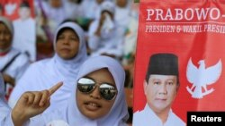 A girl sings a song as she attends Indonesia's presidential candidate Prabowo Subianto campaign rally in Gelora Bung Karno Stadium in Jakarta, June 22, 2014.