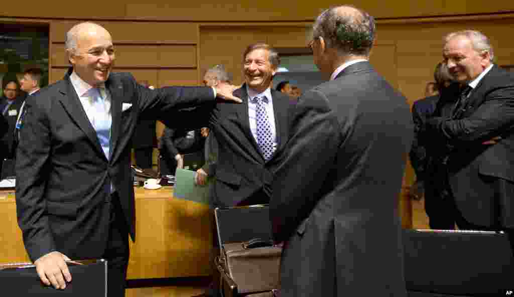 French Foreign Minister Laurent Fabius, left, speaks with Slovenian Foreign Minister Karl Erjavec, center, during a round table meeting of EU foreign ministers in Luxembourg, Oct. 20, 2014.