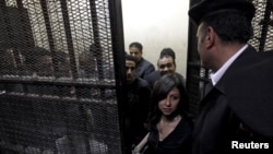 FILE - Activists, accused of working for unlicensed non-governmental organizations (NGOs) and receiving illegal foreign funds, stand in a cage during the opening of their trial in Cairo, March 8, 2012. Egypt's parliament approved a bill to regulate non-government organizations November 15.