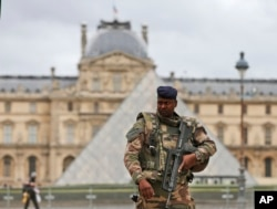 FILE - A soldier patrols in the courtyard of the Louvre Museum in Paris, Nov. 17, 2015.