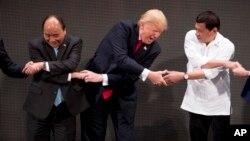 13일 필리핀에서 개막한 제31차 동남아시아국가연합(ASEN), 아세안 정상회의에서 각국 정상들이 손을 맞잡고 있다. 왼쪽부터 응우옌 쑤언 푹 베트남 총리, 도널드 트럼프 미국 대통령, 로드리고 두테르테 필리핀 대통령.