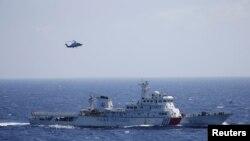 Kapal dan helikopter China dalam latihan pencarian dan penyelamatan dekat pulau Qilian Yu di Kepulauan Paracel atau Xisha, di Laut China Selatan (14/7).