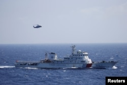FILE - Chinese ship and helicopter are seen during a search and rescue exercise near Qilian Yu subgroup in the Paracel Islands, which is known in China as Xisha Islands, South China Sea, July 14, 2016.