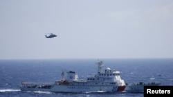 在帕拉塞尔群岛(中国称西沙群岛)进行搜救演习的中国海警船和直升机。(2016年7月14日)