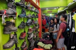 FILE - Tourists from Singapore visit the Everest Base Camp shop for trekking gear in Kathmandu, Nepal, April 20, 2016. After two hard years for mountaineering, more than 200 climbers have scaled the daunting mountain in the past 10 days, sending a wave of