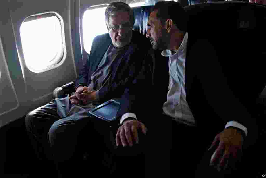 Presidential candidate and former foreign minister Zalmai Rassoul (left) and his first vice-presidential candidate, Ahmad Zia Massoud (right) speak on a plane en route to Kabul, March 30, 2014.