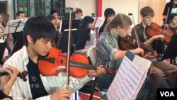 Para anggota orkestra sedang berlatih untuk sebuah pementasan.