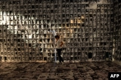 A woman stands among photos taken of human rights victims during martial law, displayed at an experiential museum inside a military camp in Manila on February 24, 2016, ahead of the 30th anniversary of people power that toppled dictator Ferdinand Marcos.