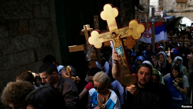 Christian worshippers hold crosses as they take part in a procession along Via Dolorosa on Good Friday during Holy Week in Jerusalem's Old City April 18, 2014. Christian worshippers on Friday retraced the route Jesus took along Via Dolorosa to his crucifi