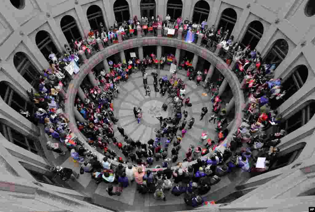 Members of the transgender community and others who oppose Senate Bill 6, protest in the exterior rotunda at the Texas state Capitol as the Senate State Affairs Committee holds hearings on the bill, in Austin, Texas.
