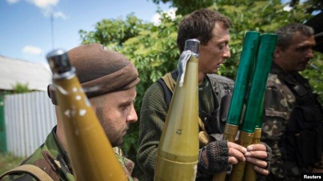 Pro-Russian separatists hold rocket-propelled grenade projectiles in Siversk, Donetsk region, June 19, 2014.