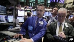 Specialist Christopher Culhane, left, works at his post on the floor of the New York Stock Exchange Tuesday, Oct. 4, 2011. (AP Photo/Richard Drew)
