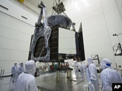 Technicians lower NASA's Juno spacecraft onto a fueling stand at Astrotech's Hazardous Processing Facility in Titusville, Florida, June 27, 2011