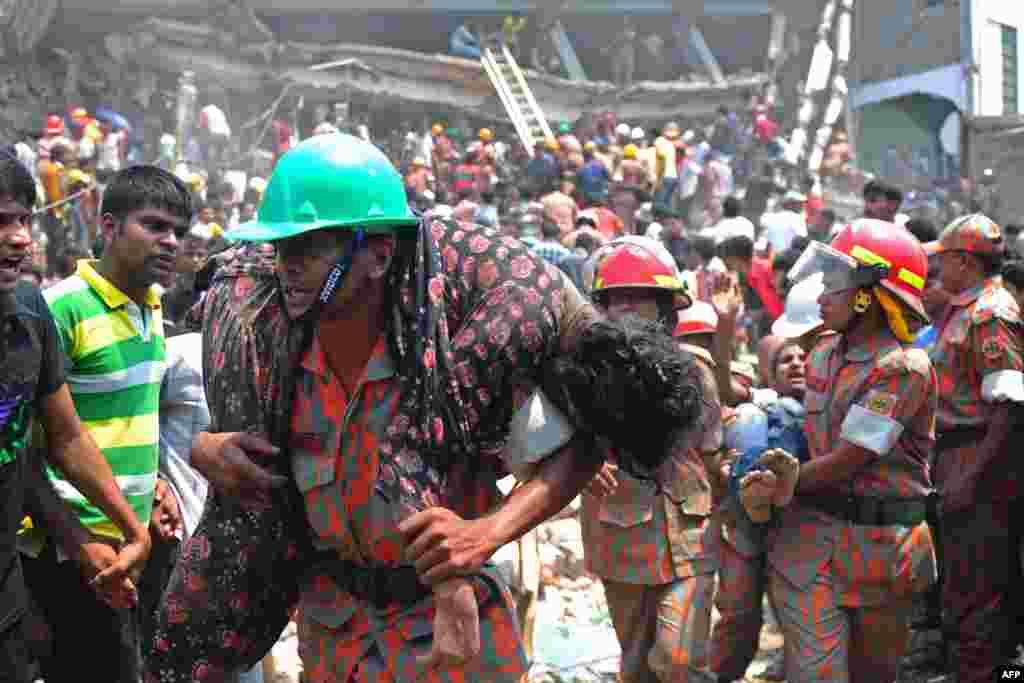 24일 방글라데시 건물 붕괴 현장에서 구조대원들이 부상자들을 이송 중이다.