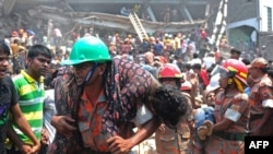 Un pompier transporte un ouvrier du textile blessé après l'effondrement d'un immeuble de huit étages à Savar au Bangladesh, le 24 avril 2013 (AFP PHOTO/Munir uz Zaman)