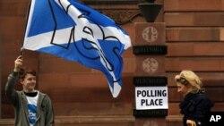 18일 스코틀랜드에서 분리독립을 묻는 주민투표가 시작된 가운데, 에딘버러 투표소 앞에서 한 남성이 찬성을 지지하는 깃발을 흔들고 있다.