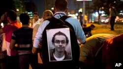 Egyptian activist with poster of slain activist Mohammed el-Gendy, who was killed during the Arab Spring uprising, at rally to withdraw confidence from Egyptian President Mohamed Morsi, Cairo, May 16, 2013.