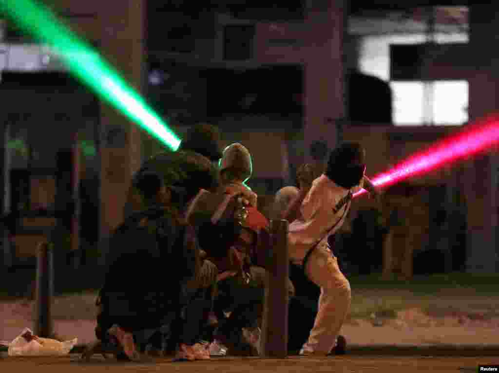 Laser beams are shot through the air as demonstrators hurl rocks during a protest demanding government action to tackle poverty, police violence and inequalities in healthcare and education systems, in Bogota, Colombia, May 10, 2021.